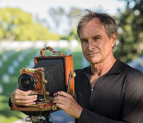 Director Jeff Crum with an antique camera at a Veterans Cemetery